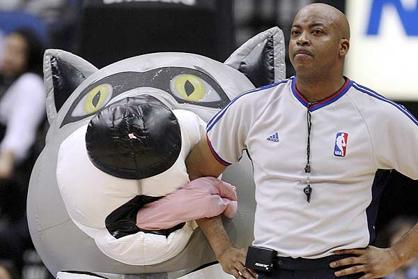 Minnesota Timberwolves mascot Chopper (left) wraps his tongue around the arm of referee Olandis Poole during a timeout in the first half of the Timberwolves' NBA basketball game against the Toronto Raptors in the Target Center in Minneapolis.