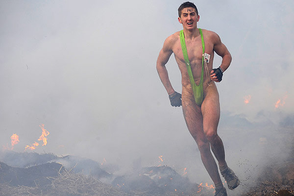 A competitor runs through a burning field during the Tough Guy event in Perton, central England.