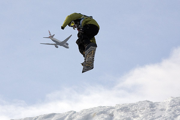 A British Airways plane flies past on its way to Heathrow Airport as Johan Gaume of France competes in the snowboarding heats at Battersea Power Station during a practice day for Freeze, the UK's biggest winter sport and music festival in London.