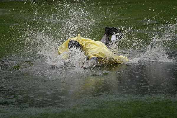 A spectator dives into a puddle after play was called for the day during the first round of the US Open golf championship on the Black Course at Bethpage State Park in Farmingdale, New York.