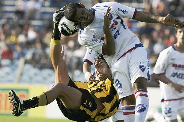 Penarol's Carlos Bueno (left) and Carlos Caballero from Nacional compete for the ball during the first half of their Uruguayan tournament.