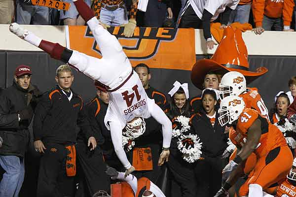 Oklahoma quarterback Sam Bradford (14) is flipped as he is knocked out of bounds short of the goal line in the third quarter against Oklahoma State defender Patrick Lavine (4) during their NCAA college football game in Stillwater, Oklahoma.