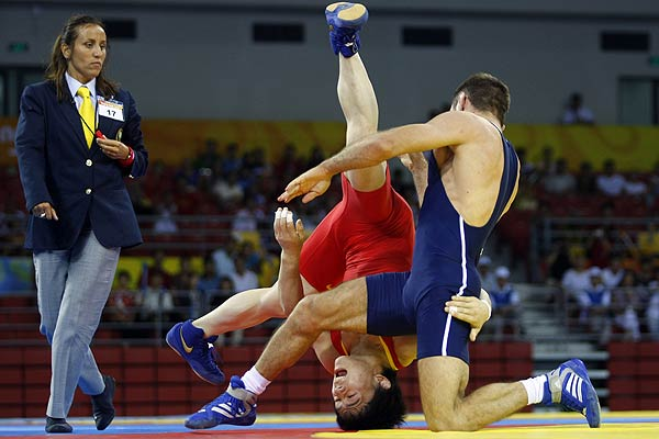 Sheng Jiang of China (in red) fights Eusebiu Iancu Diaconu of Romania during their 60kg men's Greco-Roman wrestling repechage match at the Beijing Olympics.