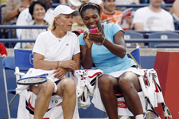 Martina Navratilova (left) looks at Serena Williams' Iphone while playing in an exhibition doubles match at the Rogers Cup tennis tournament in Toronto.