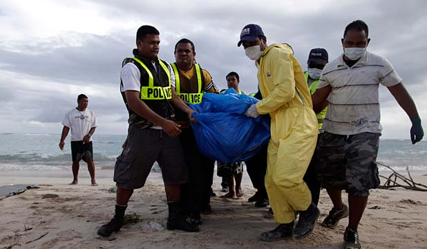 Samoan police carry the body of a tsumani victim found in the water near Matavai on the Samoa's southern coast.