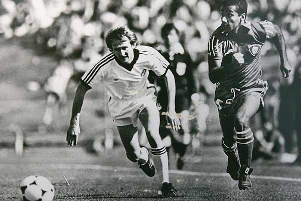 New Zealand's John Hill is in a race for the ball with a Kuwaiti player during a 1981 qualifying game for the 1982 World Cup.