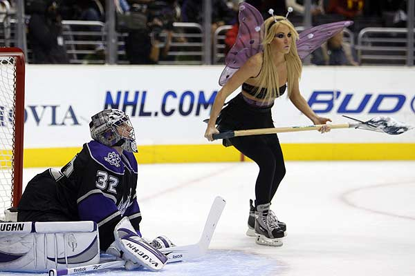 Los Angeles Kings goalie Jonathan Quick stretches during a timeout as a woman dressed in a Halloween costume cleans the ice during the first period of their NHL hockey game against the Vancouver Canucks in Los Angeles.