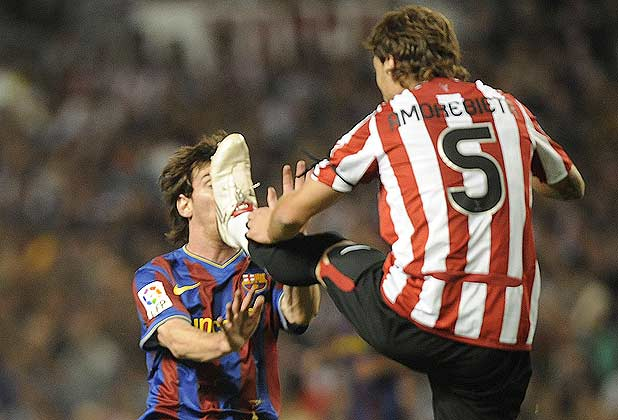Barcelona's Lionel Messi tries to avoid being kicked by Athletic Bilbao's Fernando Amoribieta.