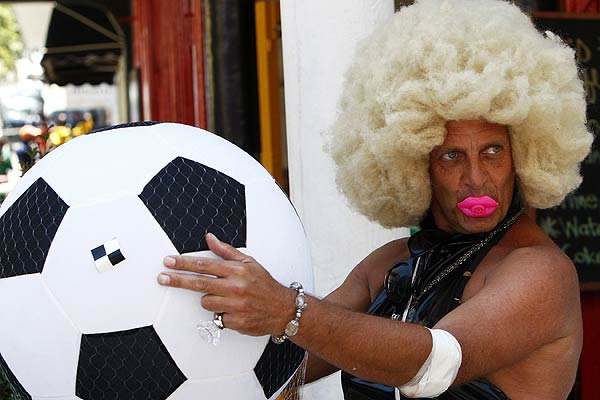 A fan poses with a giant football during celebrations in Cape Town ahead of the 2010 World Cup draw.