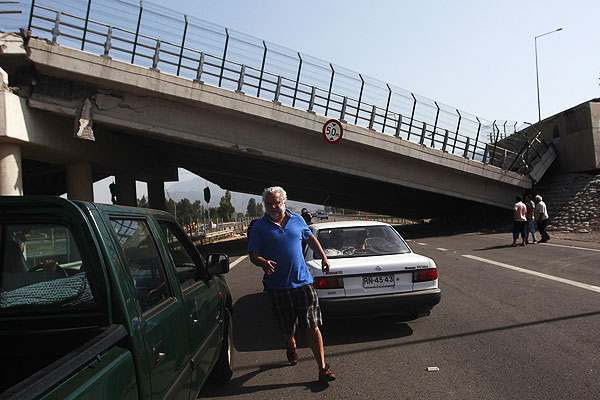 Motorists pass under a footbridge that has collapsed over the Panamerican Highway after a major earthquake in Curico, Chile.