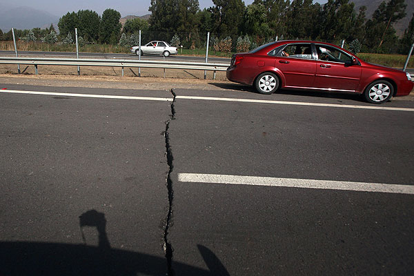 A car passes a split in the Panamerican Highway caused by a major earthquake in Curico, Chile.