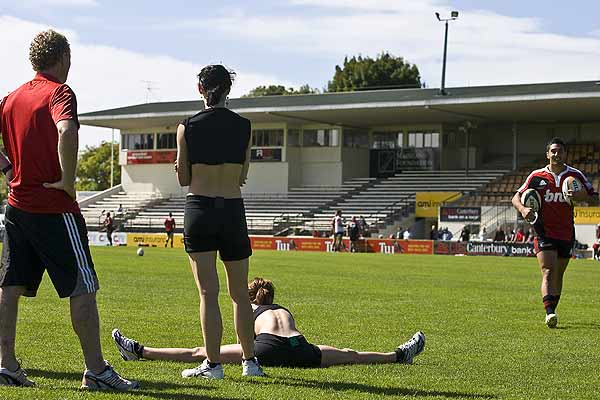 Clytie Campbell and Katie Hurst-Saxton from the Royal New Zealand Ballet watch Crusaders Daniel Bowden during training at Rugby Park, Christchurch.