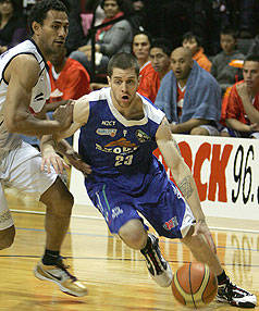 Saints' Eric Devendorf tries to drive past the Giants Mika Vukona.