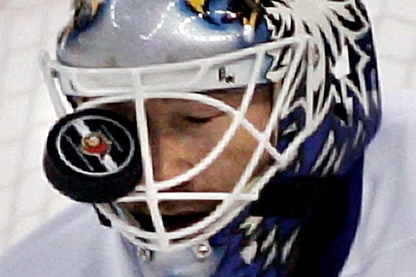 Toronto Maple Leafs goalie Ed Belfour reacts to a puck lodged in his helmet during second period National Hockey League action against the Ottawa Senators in Ottawa.