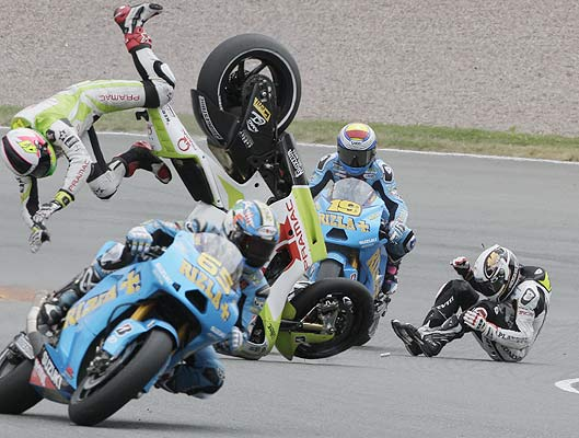 Honda MotoGP rider Randy de Puniet of France (right) and Ducati MotoGP rider Aleix Espargaro of Spain (left) crash during the German Grand Prix at the Sachsenring circuit.