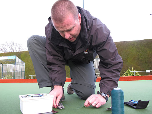 A STITCH IN TIME: Tiger Turf installation manager Spencer Myer sews up damaged caused by a vandal in the Hokonui Bowling Club's artificial turf.