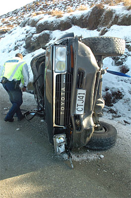 A police officer inspects a vehicle that crashed on the road to the Coronet Peak skifield.