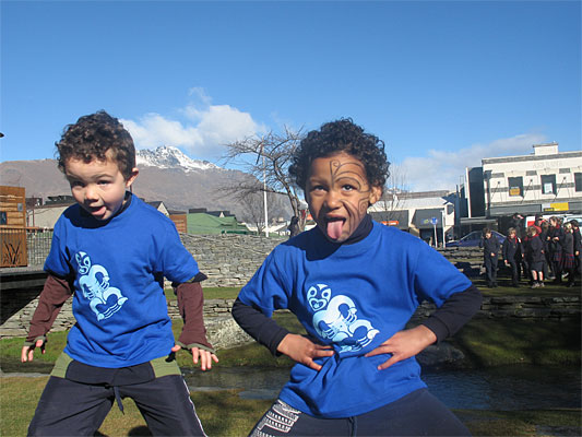 ames Scoles (left) and Ariki Moseley, both 5, of Remarkables Primary School, show how it's done, with a pukana during a Maori Language Week performance on the Village Green in Queenstown.