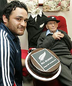 All Blacks halfback Piri Weepu presents Eric Tindill with a birthday cake to mark the