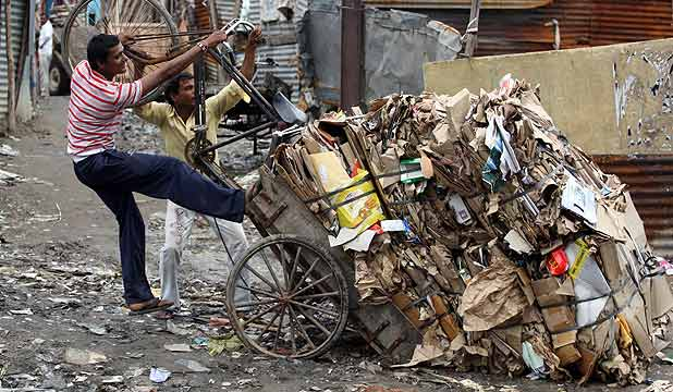 Rag pickers try to right their overturned cycle rickshaw near the 2010 Commonwealth Games athletes village in New Delhi.