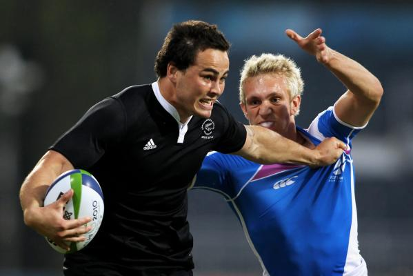 New Zealand's Zac Guildford fends off a Scottish player in the Pool A sevens match at the Delhi Commonwealth Games.