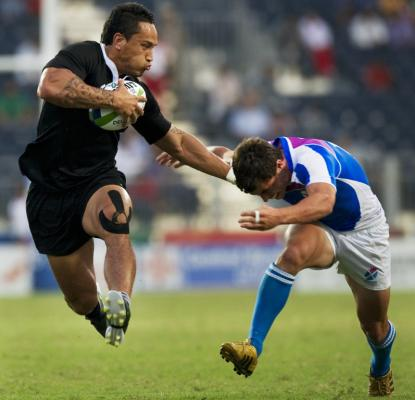 New Zealand's Hosea Gear is airborne as he fends off the tackle of a Scottish player in the Pool A sevens match at the Delhi Commonwealth Games.