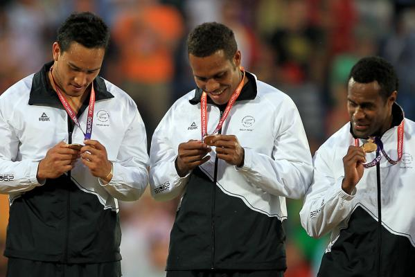 New Zealand's Hosea Gear, Tomasi Cama, and Lote Raikabula check out their gold medals after beating Australia in the Sevens rugby final at the Delhi Commonwealth Games.