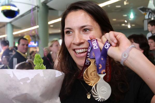 Squash gold and silver medal winner Joelle King shows her medals as members of the New Zealand Commonwealth Games team arrive home in Auckland.