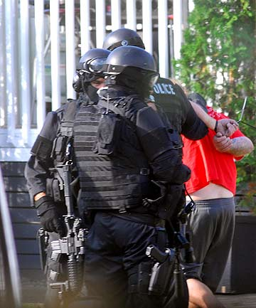 RAID: There were two vanloads of heavily-armed police at the scene.