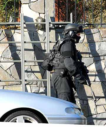 LADDERS: Police scaled the fences of the Brentwood Ave, Mt Eden property, around 7.30am.