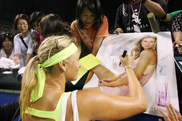 Maria Sharapova signs a poster after beating Samantha Stosur at the Toray Pan Pacific Open Tennis tournament in Tokyo in 2009.