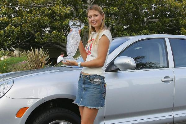Maria Sharapova poses with the Billie Jean King Trophy in front of a Porsche Cayenne the day after winning the single's title at the WTA Tour Championships Tournament in 2004 at the Fin Santa Monica, California.