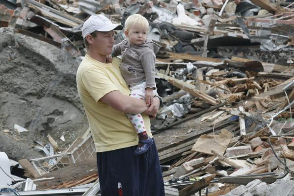 Ross Whelan and daughter Madelyne Whelan stand beside the remains of their local shops in Christchurch.