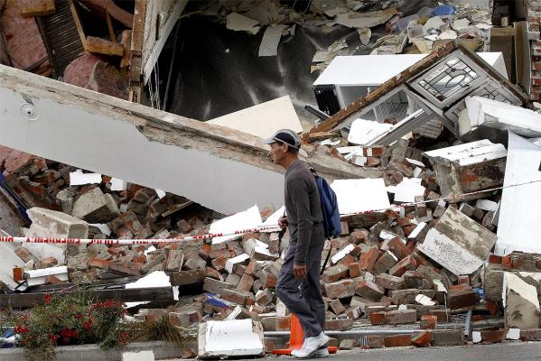 A passerby walks past the destroyed Pharmacy building on the corner of Bealey Ave and Colombo Street.