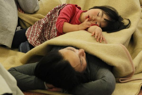 Passengers sleep at a lobby as they wait for their transportation at Haneda Airport in Tokyo, March 12, 2011.