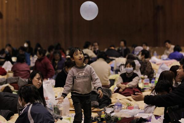 A boy plays with a balloon at an evacuation centre set in a gymnasium in Kawamata