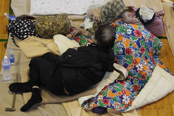 People sleep on floor at evacuation centre.
