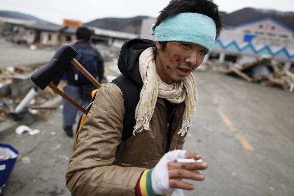 An injured survivor searches for food at a destroyed supermarket in the devastated residential area of Otsuchi.