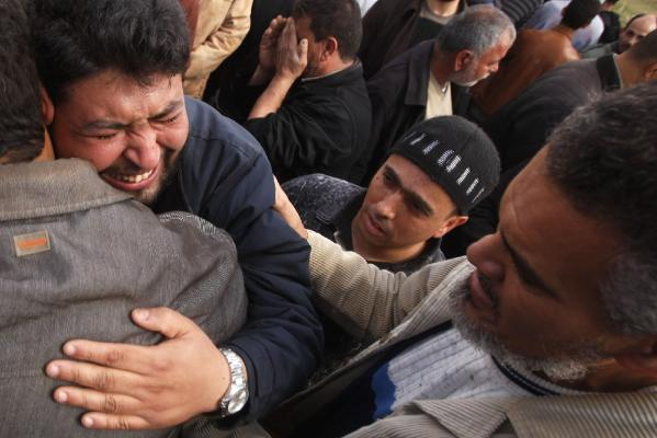 Relatives of a Libyan killed by forces loyal to Libyan leader Muammar Gaddafi mourn during his funeral in Benghazi.