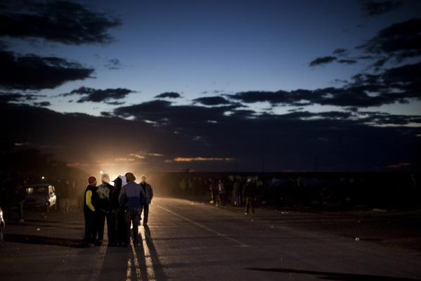 Men walk along a road near to a refugee camp set up for displaced people who recently crossed over the border from Libya into Tunisia, fleeing from the unrest in the Libya, in Ras Ajdir, Tunisia, Sunday, March 20, 2011. More than 250,000 migrant workers have left Libya for neighbouring countries, primarily Tunisia and Egypt, in the past three weeks.