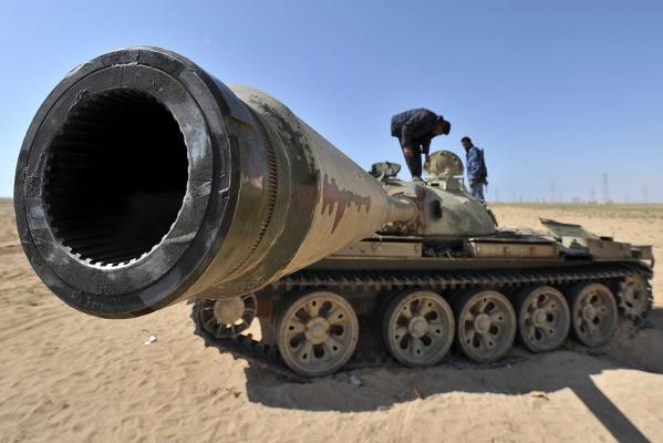 A Libyan rebel stands on an unidentified tank near the key city of Ajdabiya as loyalist forces have encircled the town.
