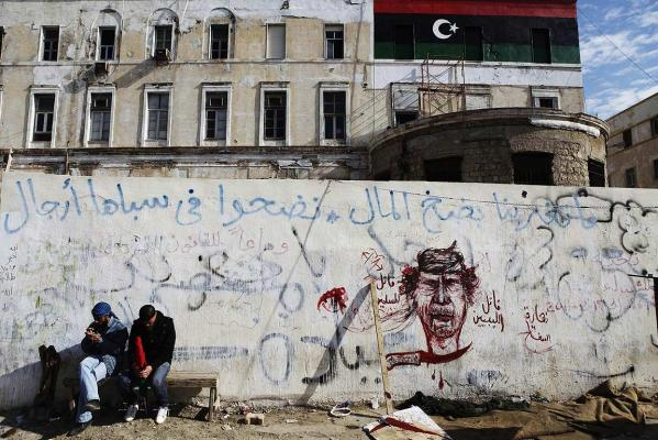 Libyan rebel supporters sit outside rebel headquarters decorated with revolutionary graffiti in the northeastern city of Benghazi.
