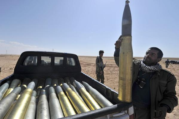A Libyan rebel fills a pick-up truck with shells from an unidentified tank near the key city of Ajdabiya.