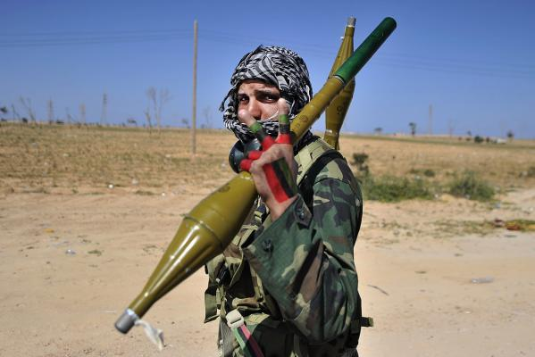 A Libyan rebel fighter flashes the victory sign as he carries rocket propelled grenades at a check point near the key city of Ajdabiya.