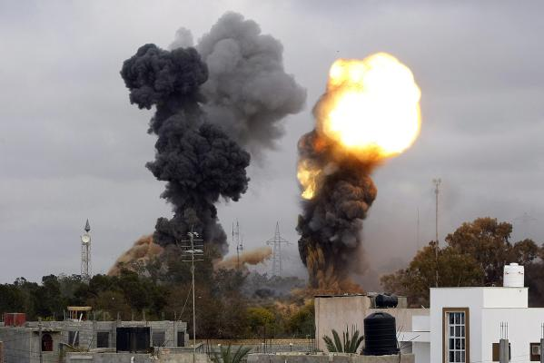Smoke billows as seven explosions rocked the Libyan capital Tripoli, some in the vicinity of the tightly-guarded residence of leader Muammar Gaddafi and military targets.