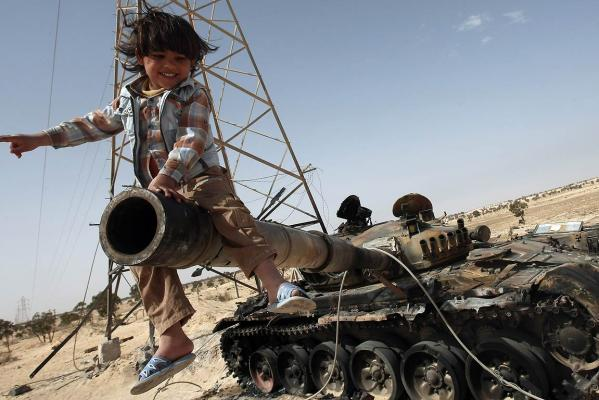 A Libyan child sits playing on the canon of a destroyed tank in the strategic oil town of Ajdabiya east of Tripoli.