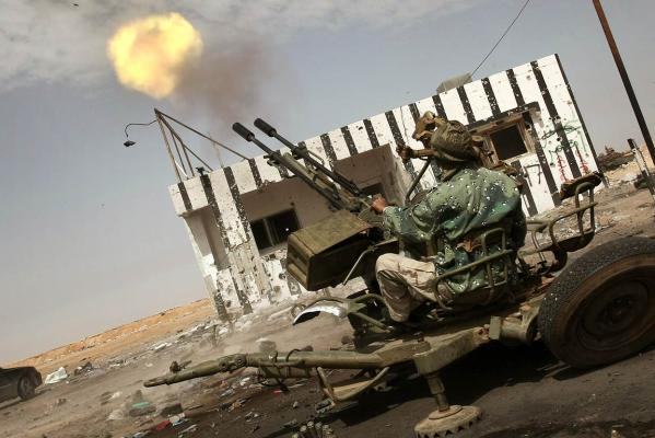 A Libyan rebel shoots an anti-aircraft machine gun in Ajdabiya.