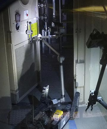 A radio-controlled PakBot robot opens a door inside housing for the reactor of Unit 3 during inspection of the tsunami-damaged facilities at the Fukushima Dai-ichi Nuclear Power Plant.