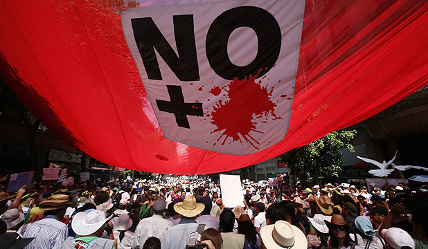 MARCH AGAINST VIOLENCE: Demonstrators march under a banner with a message reading,