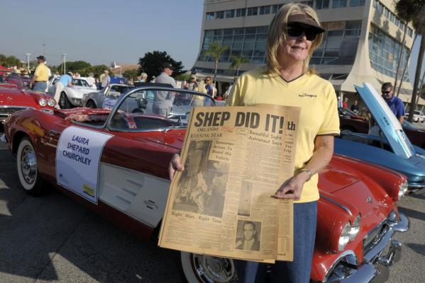 Lloyce Campbell of Florida holds a laminated front page of the Orlando Evening Star which was autographed by US space pioneer astronaut Alan Shepard, while standing in front of a '61 Corvette at the start of the parade commemorating Shepard's historic flight 50 years ago in Cocoa Beach.